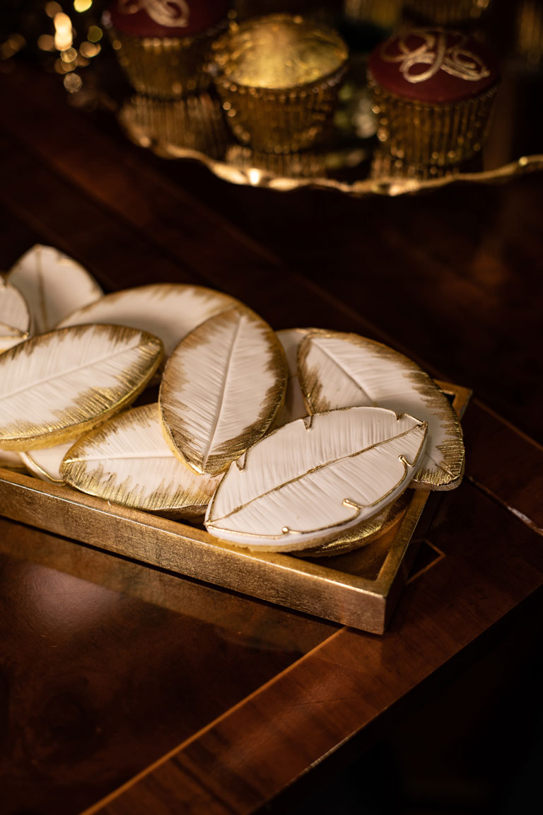 A selection of elegant leaf shaped cookies by GC Couture with gold piping around the edges