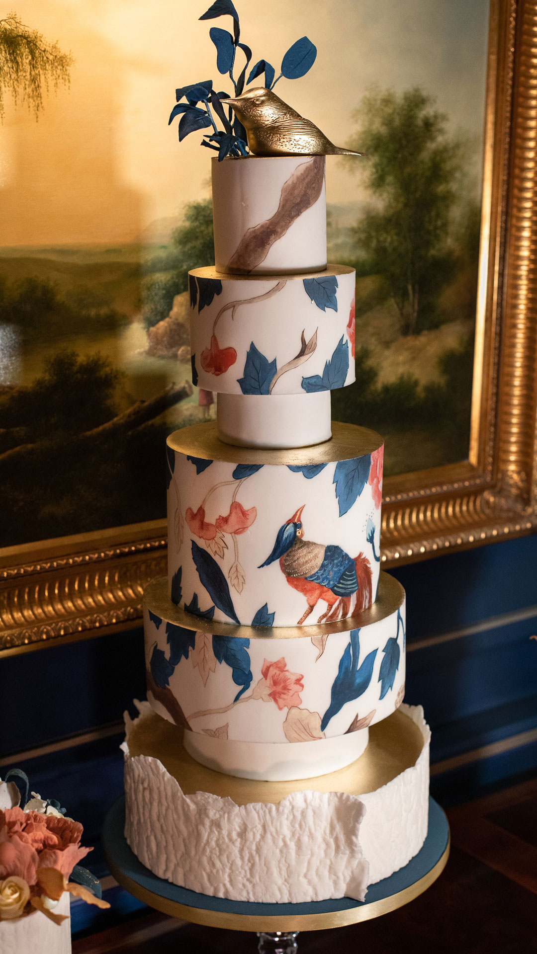 An elegant 5-tier centrepiece wedding cake or corporate cake at The Stafford London with hand painted bird and leaf designs throughout the cake relating to the decor of the dining chairs in The Game Bird restaurant