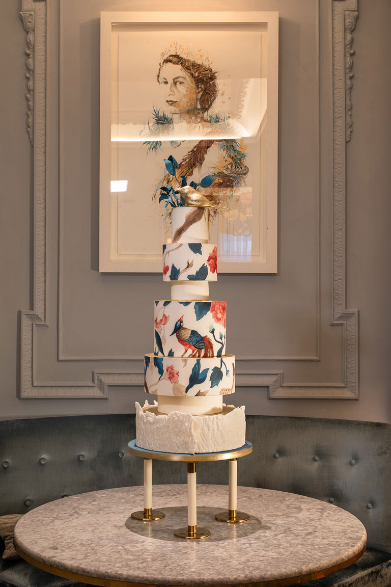 Sat on a table in The Game Bird Restaurant is GC Couture's 5-tier cake in front of a painting of Her Majesty the Queen