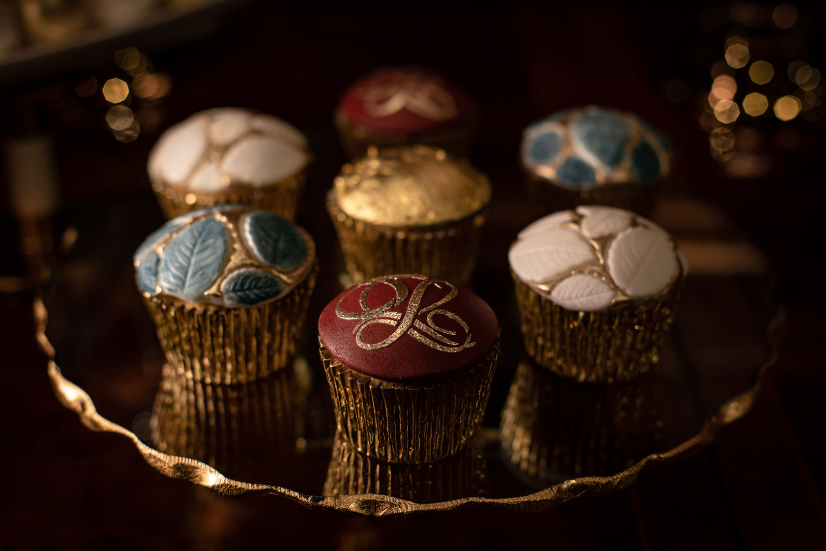 Red, blue, white and gold cupcakes By GC Couture with a delicately handpainted logo on the cupcake at the forefront