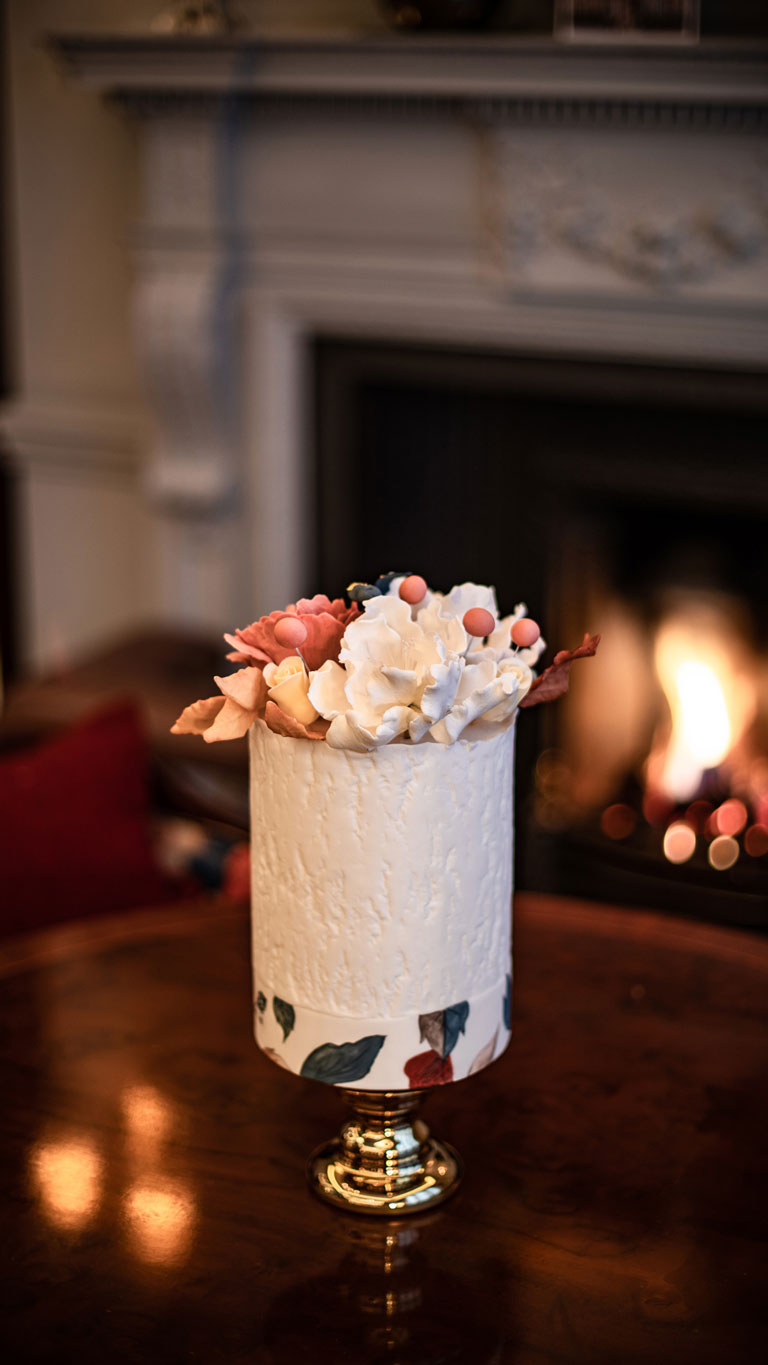A white bark effect cake topped with hand-crafted sugar flowers in front of the fireplace by GC Couture.